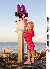 standing little girl by telescope