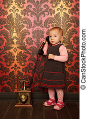 Standing little girl speaking on retro phone. Interior in...