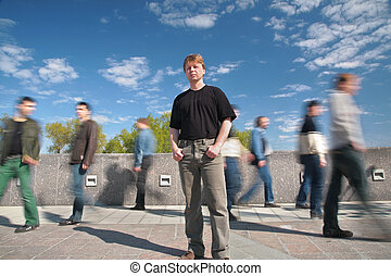 standing man among moving pedestrians