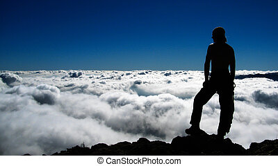 man on the cliff in mountains above clouds