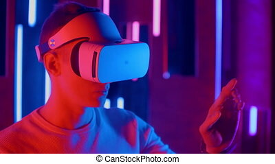 Standing man trying VR headset in neon lights.