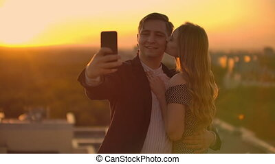Standing on the roof at sunset a married couple a man and a woman hug and take a selfie on the phone. Take pictures of yourself standing on the roof and hug. Young people in love.