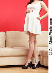 Standing pregnant woman in white dress