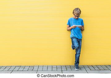 standing, ragazzo, mobile, giallo, telefono cellulare, fuori, parete