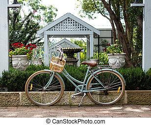 standing, signore, bicicletta, giardino, parete, lussureggiante, contro, cesto, verde, retro, fondo, trattenendo, mattone, arbusti