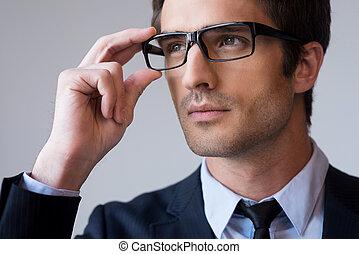 standing, successful., regolazione, giovane, formalwear, grigio, dall'aspetto, fiducioso, mentre, suo, contro, fondo, ritratto, uomo, lontano, occhiali