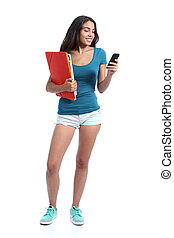 Standing teen girl holding folders and texting in a smart phone