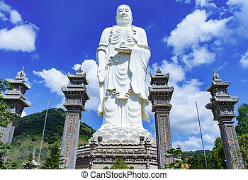 standing white Buddha on a background of blue sky