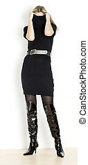 standing woman wearing black dress and fashionable boots