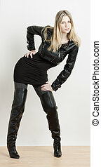standing woman wearing fashionable black boots