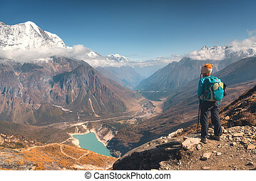 Standing young woman on the mountain peak against lake