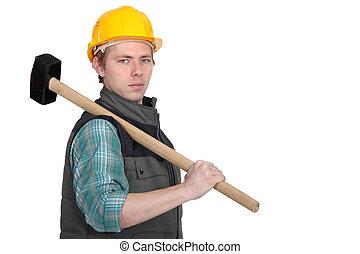 Standoffish tradesman holding a mallet