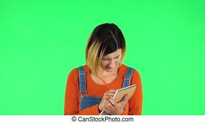 stands, girl, écrit, alors, attentivement, notebook., vert, ...