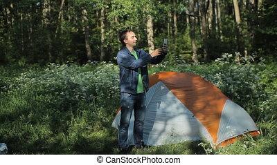 stands, selfie, matin, tôt, forêt, téléphone., homme, confection, tout, tente