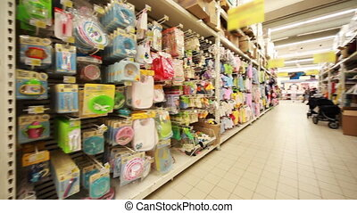 Stands with children's goods in hypermarket, panorama from left to right