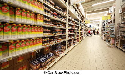 Stands with food in hypermarket, panorama from left to right