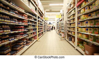 Stands with food in hypermarket, shooting from fast moving between them camera