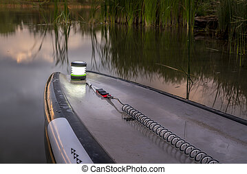 standup up paddleboard with a lantern at dusk