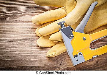 Staple gun safety gloves on wooden board construction concept