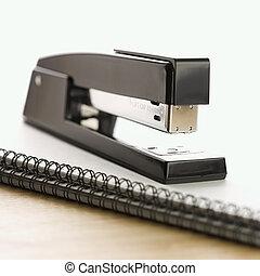 Stapler on notebook.