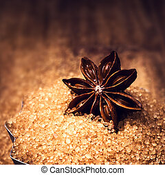 Star Anise and  brown cane sugar on wooden background, close up.