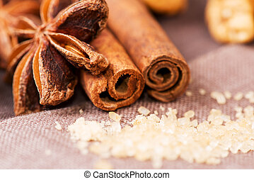 Star anise, brown sugar with cinnamon at christmas time on cloth background