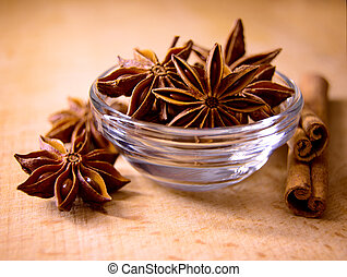 Star Anise in the Glass Bowl and Cinnamon Sticks on the Wooden Table
