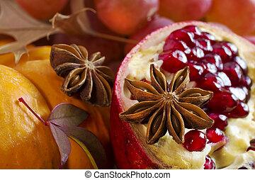 Orange pumpkin, star anise and pomegranate closeup .