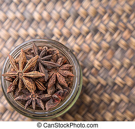 Star anise spice in a mason jar over wicker background