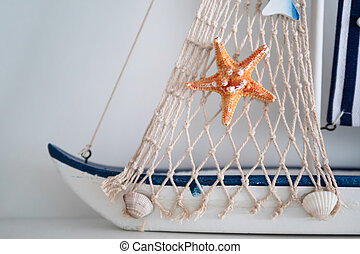 Star fish and net with shell on the boat