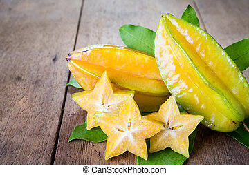 star fruit - Star fruit with green leaf on wood background ....