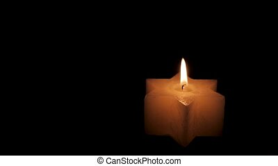 A lighted Jewish yellow candle in the shape of a star of David on Hanukkah. On a black isolated background close up in 4K without faces of people.