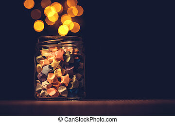 Star origami in glass jar with a festival light , symbol for gift celebration in happy time for new year concept
