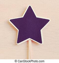 Star shape blackboard on wood with retro filter effect