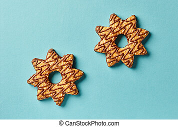 star shape cookies on blue paper background, top view