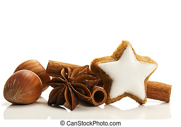 star shaped cinnamon biscuit with cinnamon sticks and hazelnuts on white background