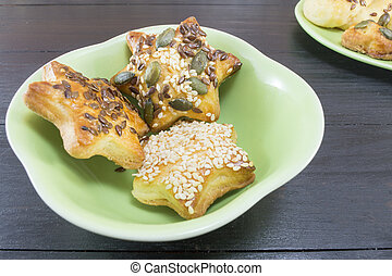 Star shaped pastry with seeds in a green plate