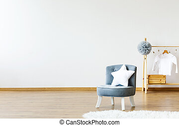 Star shaped white pillow placed on small armchair standing in white baby room interior with grey pompom and white shirt on wooden hanger. Empty wall for your poster