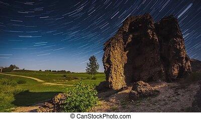 Star trails moving timelapse over the old huge rock in ...