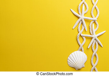 Starfish, shell and rope on a plain yellow background