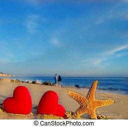 Starfish with hearts on the sandy beach