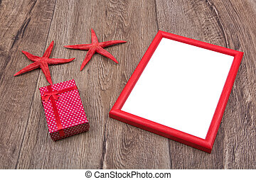 Starfishes, gift and picture frame on a wooden background