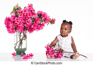 A African infant dresed in white on the table and play with pink flowers.