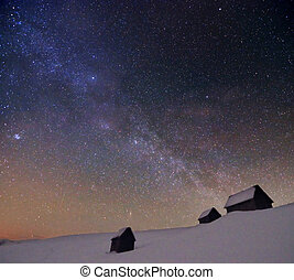 starry cloudy sky with milky way above abandoned huts