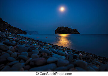 Starry night with a full moon over sea with rock in front. Cape Fiolent, Jasper beach rock of the holy phenomenon with a cross on the background of the moon