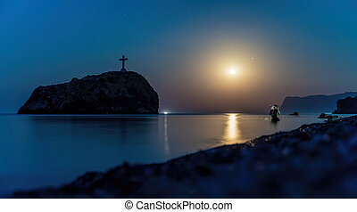 Starry night with a full moon over sea with rock in front. Cape Fiolent, Jasper beach rock of the holy phenomenon with a cross. The concept of calmness, silence and unity with nature.