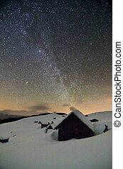 starry sky above abandoned huts in the mountains