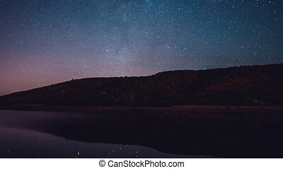 Starry sky over mountain and river at night.Constellations...