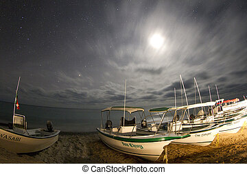 stars at night of the ocean and boats in baja california sur...