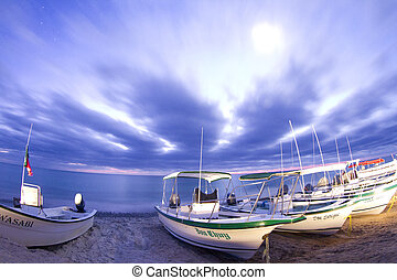 stars at night of the ocean and boats in baja california sur, mexico